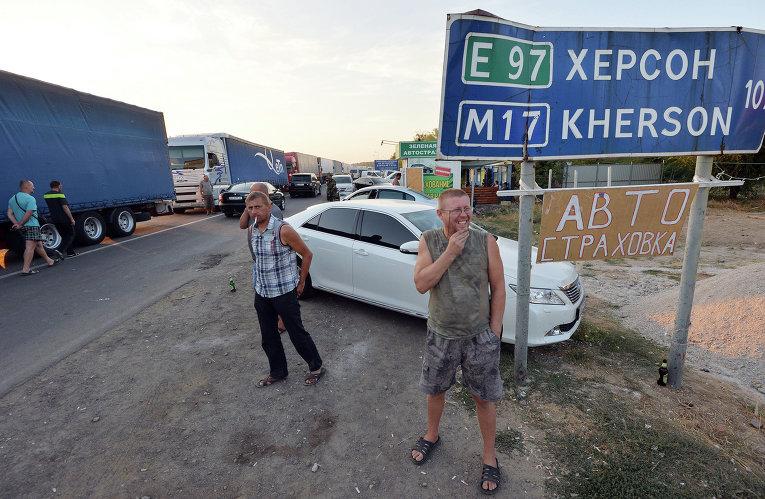 Водители наблюдают, как активисты заблокировали автодорогу на границе Украины и Крыма. 20 сентября 2015