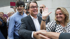 Председатель правительства Каталонии, кандидат от партии Junts pel Si (Вместе за Да) Артур Мас (в центре) с женой Хеленой Ракошник в день выборов в парламент Каталонии. Архивное фото