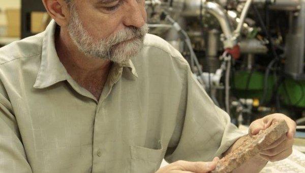 Марк Харрисон изучает образец австралийских горных пород