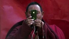 Буддистский монах снимает на смартфон во время дневных песнопений, Тибетский автономный район, КНР