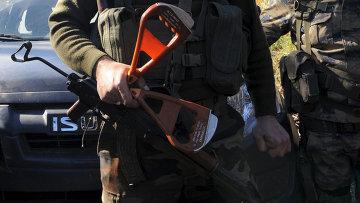 Вооруженный сирийский туркмен держит ручки катапультируемого кресла погибшего летчика Су-24