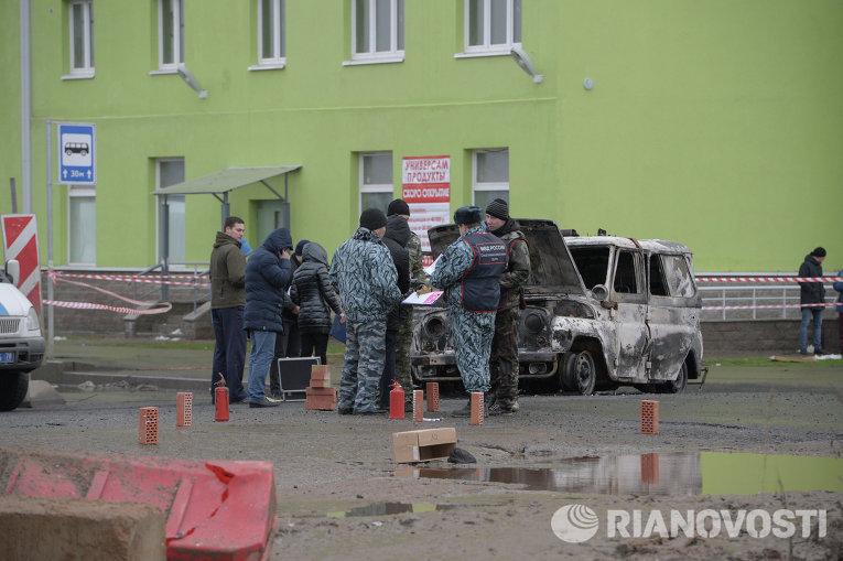 Представители правоохранительных органов осматривают место происшествия с полицейской машиной