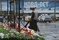 Москвичи и гости столицы приносят цветы и свечи к зданию Театрального центра на Дубровке