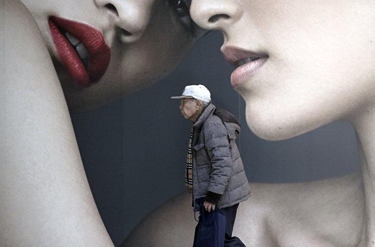 Мужчина на фоне рекламного баннера в Токио