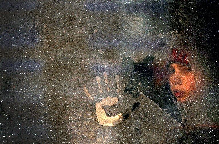 Мальчик смотрит через замерзшее окно автобуса в Минске