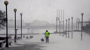 Работник коммунальной службы на набережной Спортивной гавани во время снежного циклона во Владивостоке