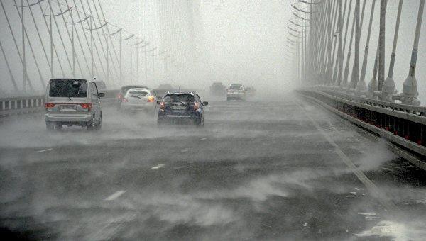 Автомобили едут по вантовому мосту через бухту Золотой Рог во время снежного циклона во Владивостоке