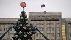 Рабочие украшают новогоднюю елку, установленную у Счётной Палаты РФ, в Москве. Архивное фото