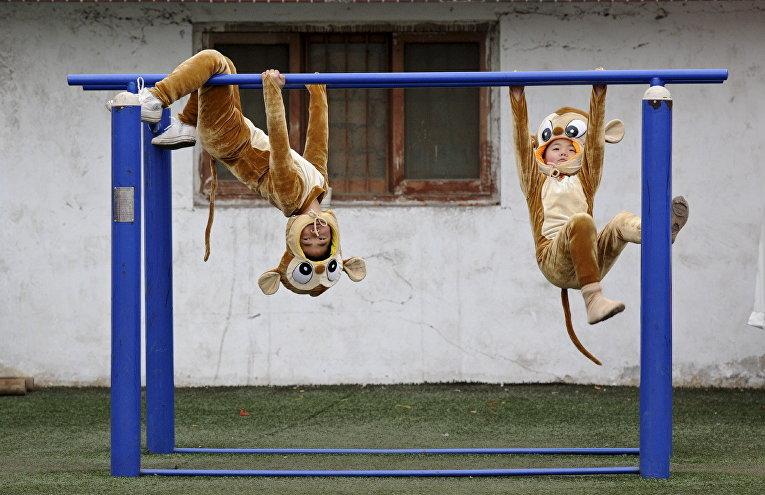 Дети в костюмах обезьян на фестивале Shehuo в провинции Шаньси, Китай
