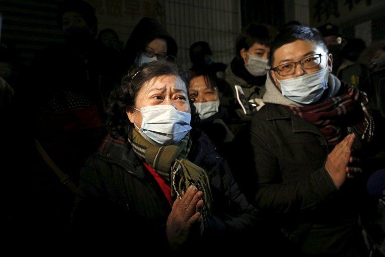 Родственники молятся за людей, которые были внутри жилого дома, рухнувшего впоследствии землетрясения на Тайване, 6 февраля 2016