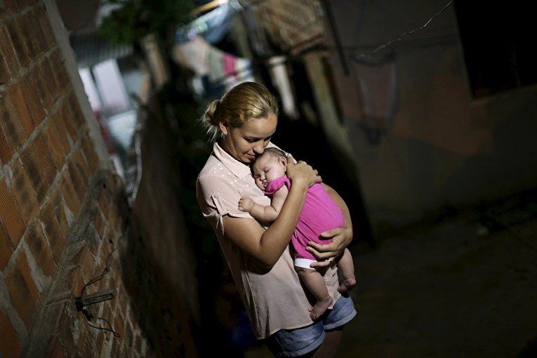 Мать держит свою больную микроцефалией дочь в Ресифи, Бразилия