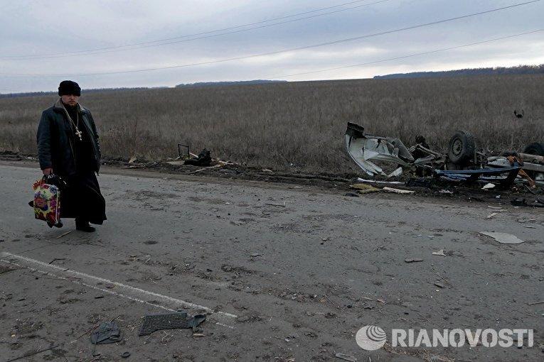Священнослужитель у места подрыва микроавтобуса в Донецкой области