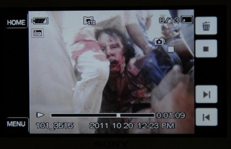 Фотография экрана мобильного телефона с изображением захваченного ливийского лидера Муаммара Каддафи в Сирте, Ливия. Октябрь 2011