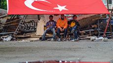 Молодые люди сидят под флагом Турции. Архивное фото