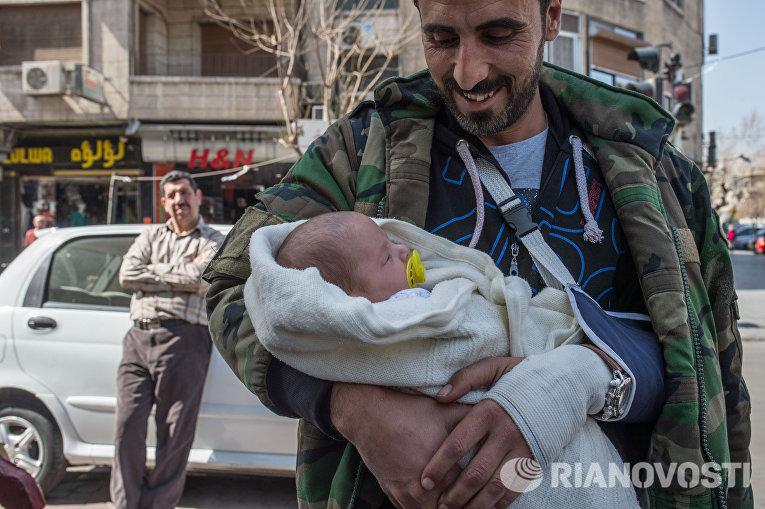 Мужчина с грудным ребенком на улице Дамаска в первый день перемирия