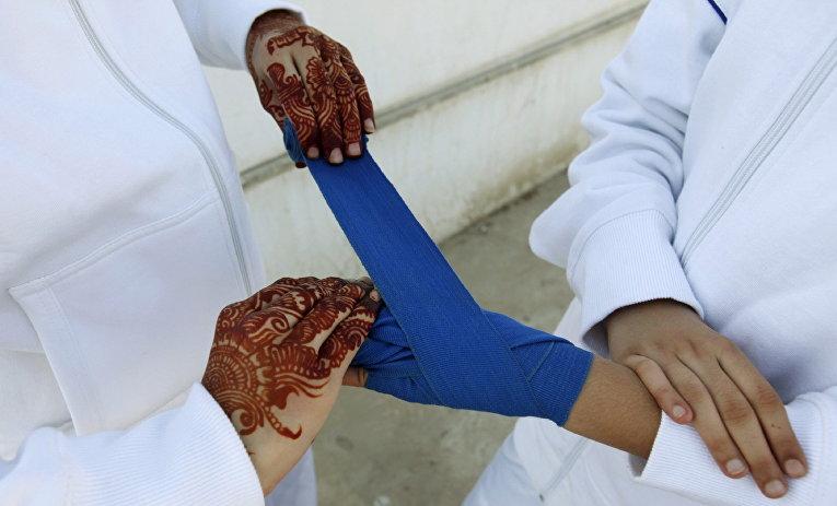 Девочка обматывает бинтами руки подруги на боксерском турнире среди девочек в Карачи, Пакистан