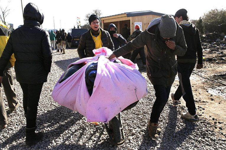 Беженцы во время сноса лагеря мигрантов в Кале, Франция. 29 февраля 2016