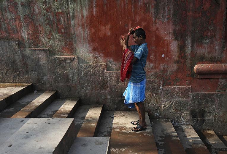 Человек расчесывает волосы после принятия ванны в Калькутте, Индия. 3 марта 2016