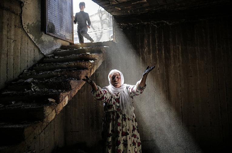 Женщина среди руин в результате боев между правительственными войсками и курдскими боевиками в городе Джизре, Турция. 2 марта 2016 года