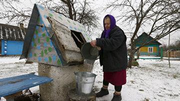 Женщина набирает воду из колодца в Белоруссии. Архивное фото