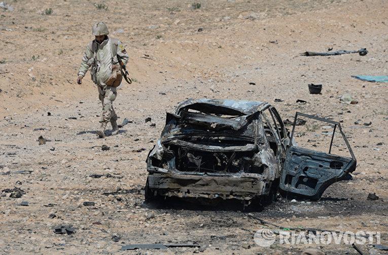 Бойцы отряда народного ополчения Соколы пустыни у военной и гражданской техники подбитой в результате боев в 10-ти км к западу от Пальмиры.