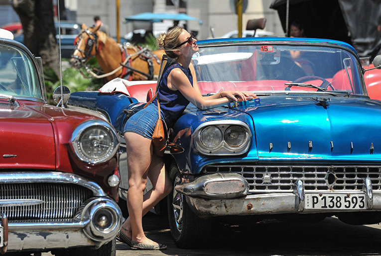 Девушка фотографируется с ретро-автомобилем в Гаване