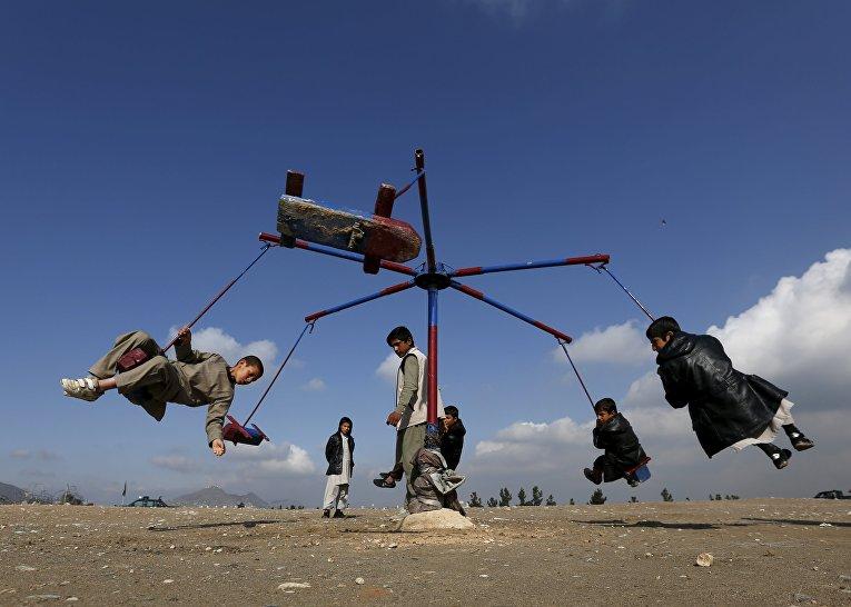 Афганские мальчики катаются на карусели во время празднования афганского Нового года в Кабуле
