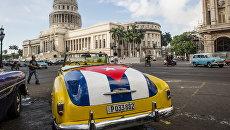 Классический американский автомобиль с изображением кубинского флага возле здания Капитолия в Гаване, Куба. Архивное фото