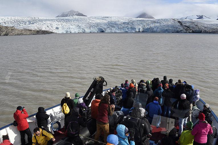 Туристы смотрят на ледник на архипелаге Свальбард в Северном Ледовитом океане, 19 июля 2015