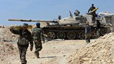 Бойцы сирийской армии во время наступления при поддержке отрядов ополчения на город Эль-Карьятейн. Архивное фото