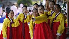 Студенты в национальных корейских костюмах во время празднования дня совершеннолетия в Южной Корее