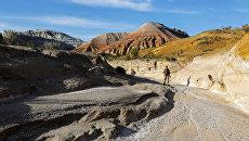 Фотограф ходит по горному хребту Актау в национальном парке Алтын-Эмель, Казахстан. 13 мая 2016