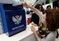 Посетительница XX Петербургского международного экономического форума опускает открытку в ящик Почты России