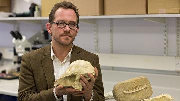 Николас Лонгрич держит череп древнего животного