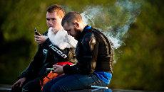 Молодые люди курят электронные сигареты на смотровой площадке Воробьевых гор в Москве. Архивное фото