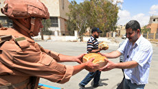 Раздача хлеба российскими военнослужащими сирийцам. Архивное фото