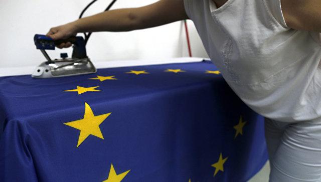 Швея гладит флаг Евросоюза на фабрике в Белграде, Сербия. Архивное фото