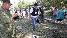 Представители Специальной мониторинговой миссии (СММ) ОБСЕ осматривают воронку от снаряда во время фиксации разрушений в Ясиноватой в Донбассе в результате обстрела города со стороны украинских силовиков