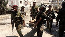 Бойцы сирийской армии выносят раненого