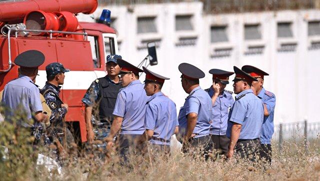 Сотрудники правоохранительных органов на месте взрыва автомашины марки Mitsubishi Delica, протаранившей ворота дипломатического представительства Китая в Бишкеке
