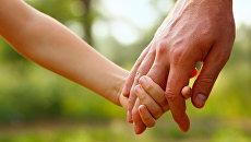 Ребенок держит за руку взрослого