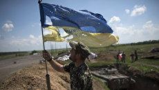 Украинский военный устанавливает флаг Украины в Марьинке недалеко от Донецка. Архивное фото