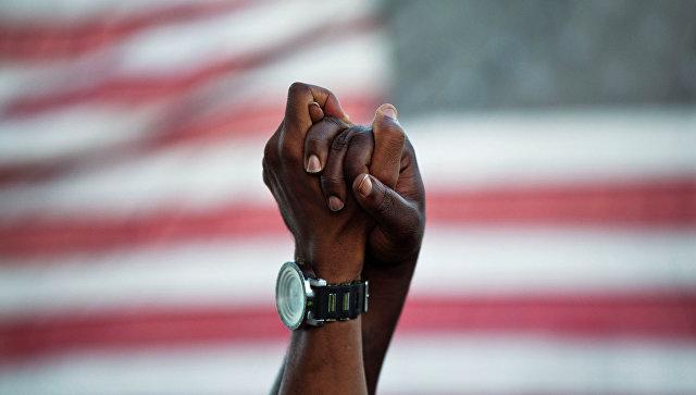 Люди держатся за руки на фоне американского флага. Архивное фото