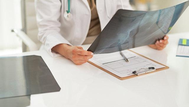Врач изучает рентгеновский снимок пациента. Архивное фото
