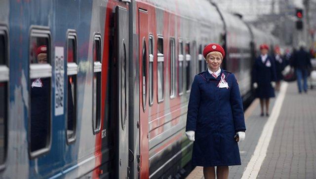 Сотрудница ОАО Российские железные дороги у поезда Россия рейса Москва – Владивосток на Ярославском вокзале в Москве