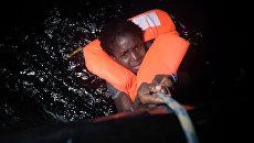 Мигрант во время спасательной операции. Архивное фото