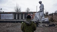 Боец ополчения ЛНР возле памятника павшим в годы Великой Отечественной войны, Луганская область. Архивное фото