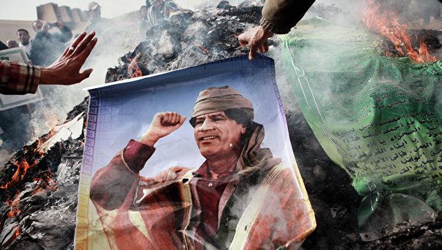 Житель Бенгази сжигает портрет Муаммара Каддафи. Архивное фото
