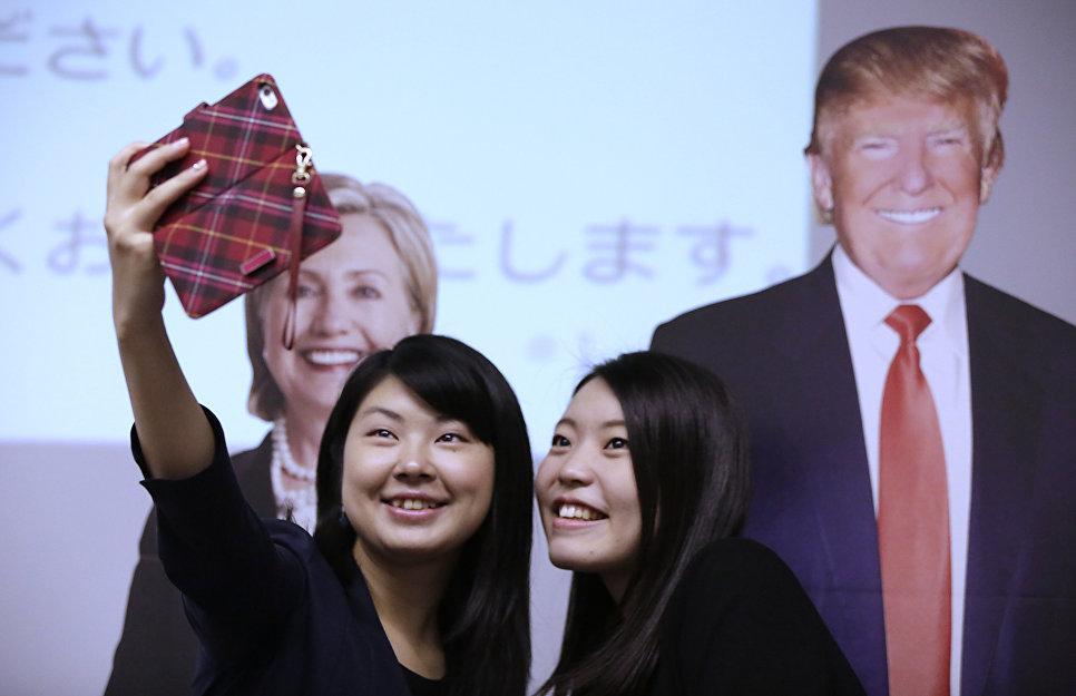 Студентки фотографируются на фоне изображений Дональда Трампа и Хиллари Клинтон в посольстве США в Токио
