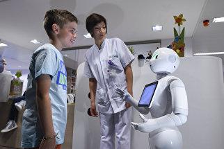 Мальчик разговаривает с роботом Pepper в городе Льеж в Бельгии